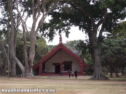 Maori Whare or meeting house at Waitangi. Beneath trees with exterior carvings